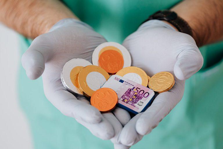 Handen gevouwen in vorm van een hart met geld er in