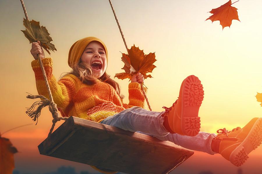 Herfst plezier - meisje op een schommel met herfstbladeren in haar hand